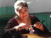A woman working in the SKIP artisan collective, making a piece of jewelry to sell to supplement her family's income. SKIP provides training workshops to mothers to teach them how to make handicrafts, which are then sold on SKIP's website and in shops around Trujillo that cater to tourists. Paola attends many of these workshops and sells her bracelets for 10 soles each.
