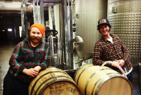Brewers leaning on casks
