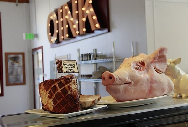 "A pig head on a counter and a sign that reads ""OINK"""