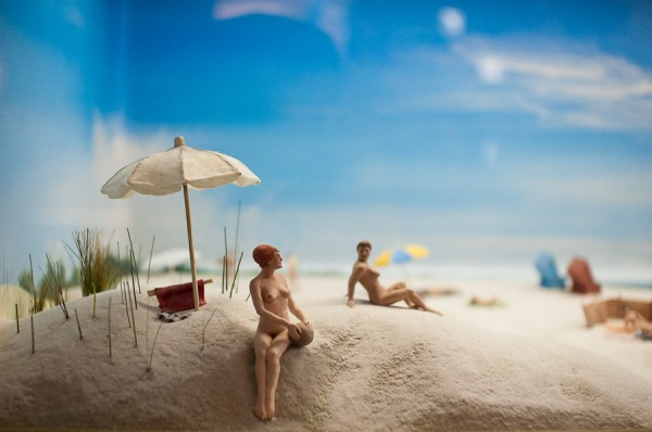 Tiny nude figurines at a beach