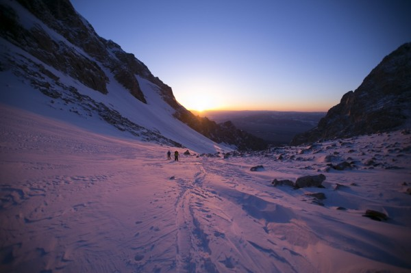 Small figures walking in the mountains at sunrise