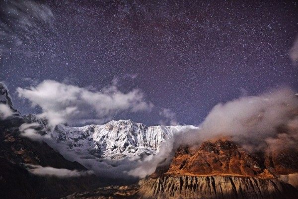 A night sky with many tiny stars and mountains partly covered by clouds