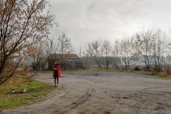 A woman in a red coat on the side of the road