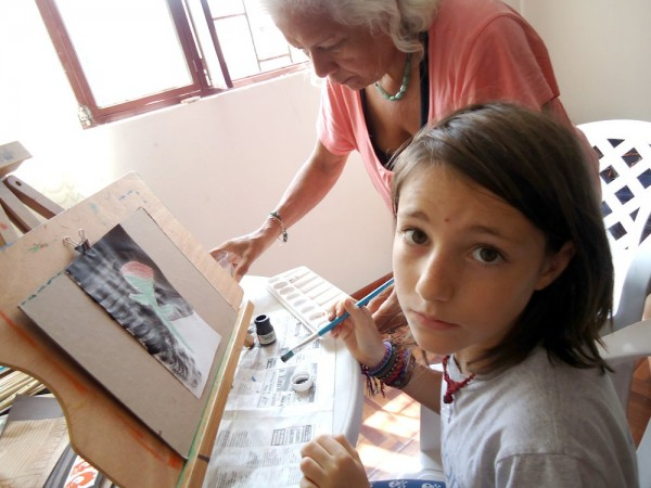 A young person painting with another person