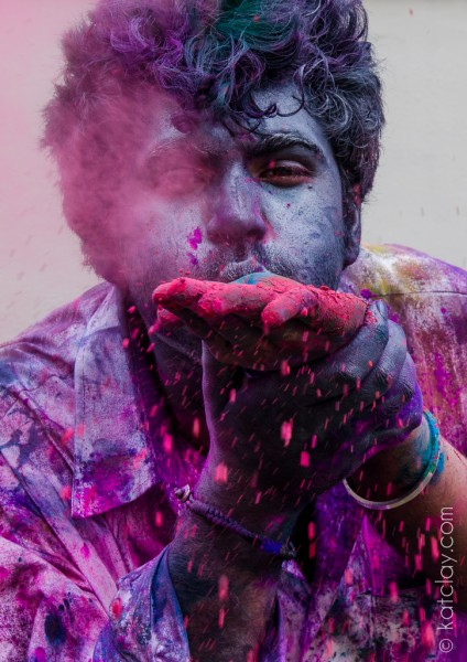 A person blowing purple powder at the camera