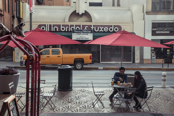 "Like New York before it, Los Angeles has developed a strong culture of ""sidewalk cafes,"" built for quick eating while commuting by foot. Here, two pedestrians spend a few minutes eating food from the Grand Central Market before going on their way."