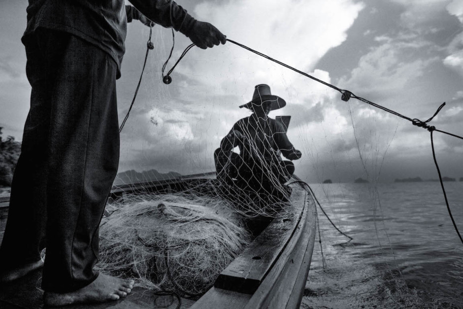 Photo: Fishermen haul in their net in the Andaman Sea.