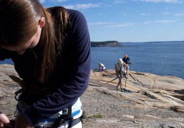 Hooking up a climbing harness in Bar Harbor, Maine