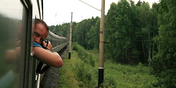 Photographer leaning out of train window