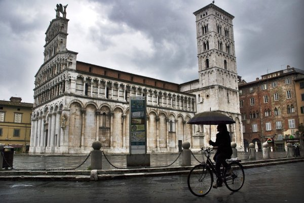 Woman cycling with umbrella in Lucca, Italy