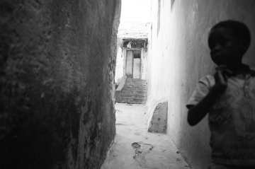Boy running in alley, Kenya