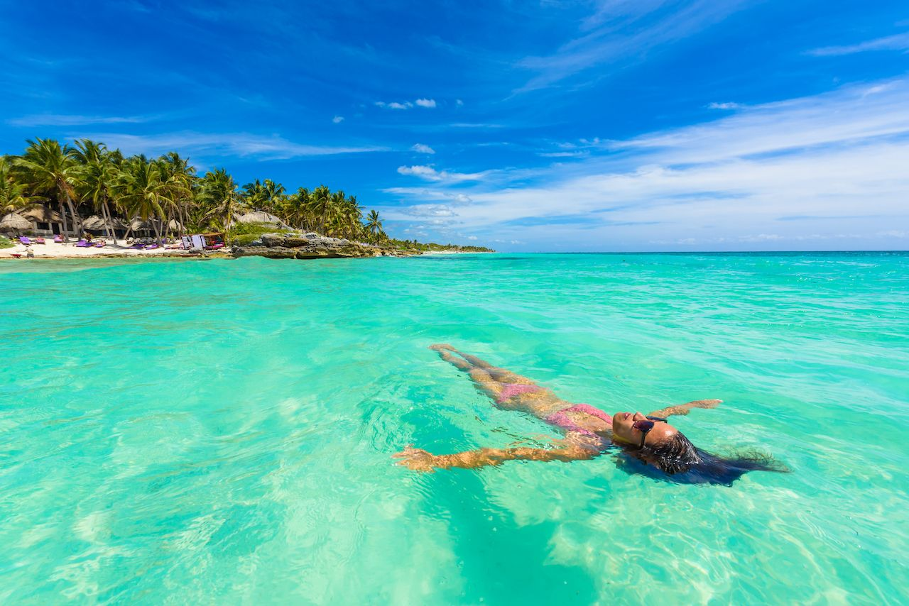 Female traveler bathing in the clear waters of the Caribbean in Tulum Mexico