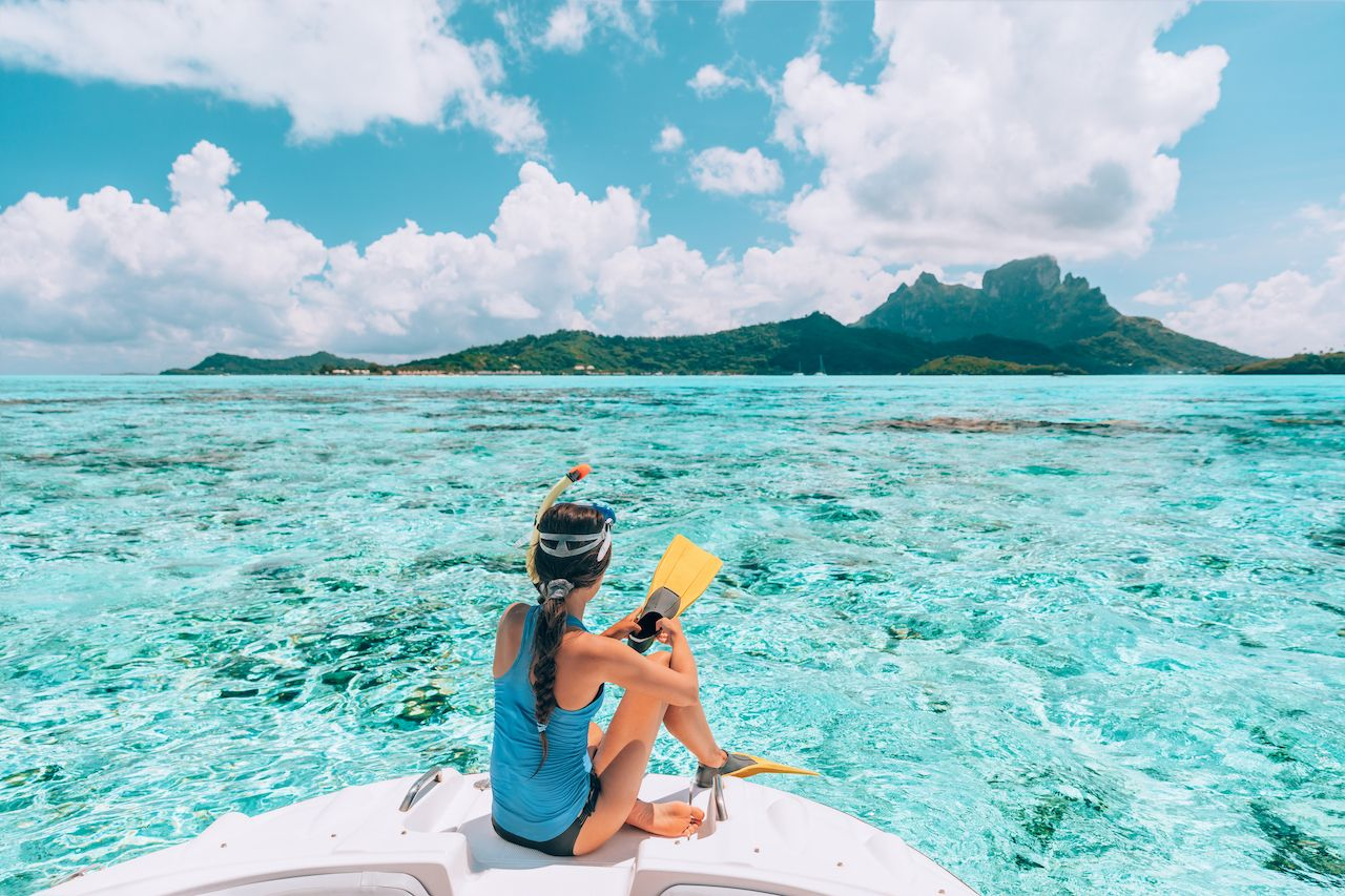 Female traveler ready to snorkel in the clear waters of Bora Bora island with coral reefs