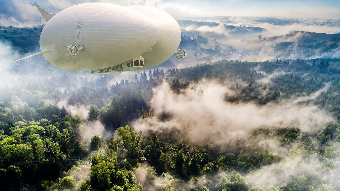 Airlander 10 Hybrid Air Vehicle flying above forest