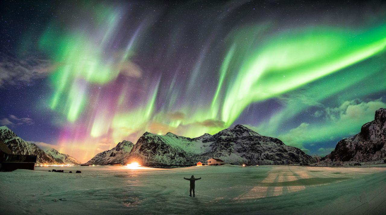 Aurora borealis over mountain with one person at Skagsanden beach, Lofoten islands, Norway