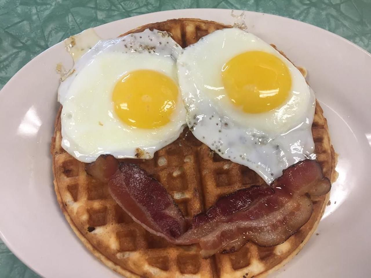 Tastee Diner overeasy eggs and a strip of bacon arranged on top of a waffle like a smiley face, best breakfast in asheville