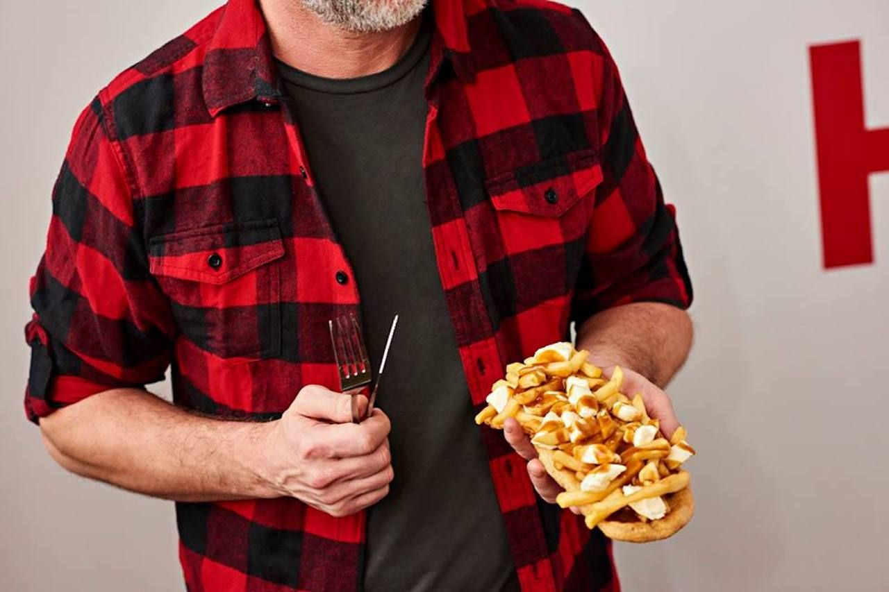 Man holding a Beaver Tails topped with poutine