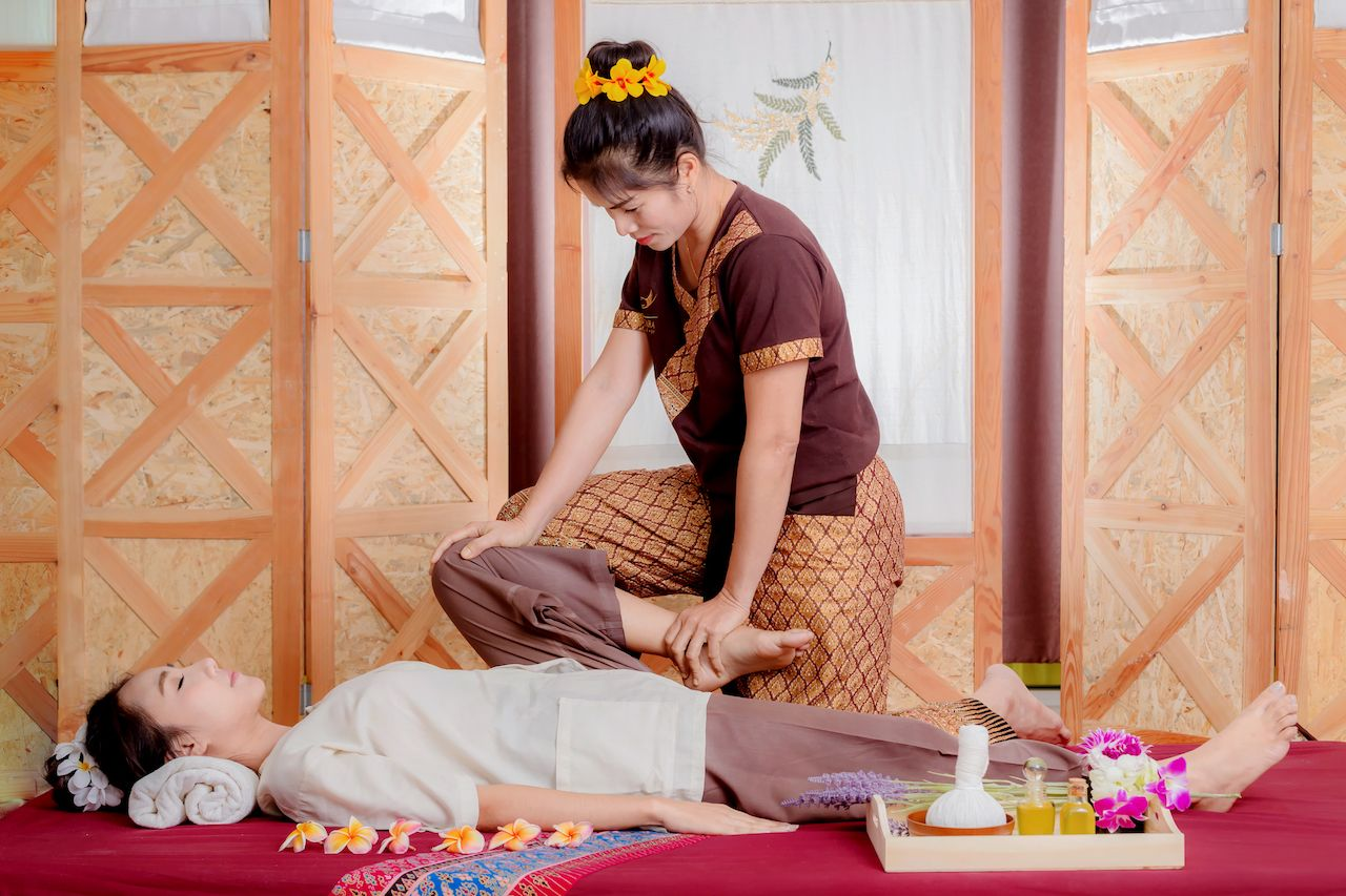 Thai masseuse doing massage for woman in spa salon, what is a thai massage