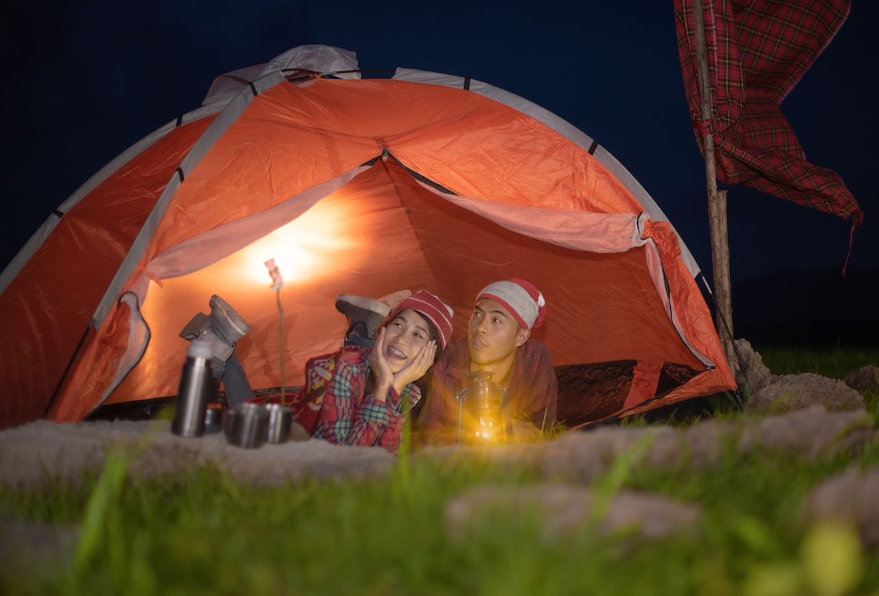 A couple uses lamps in their tent to camp without a fire