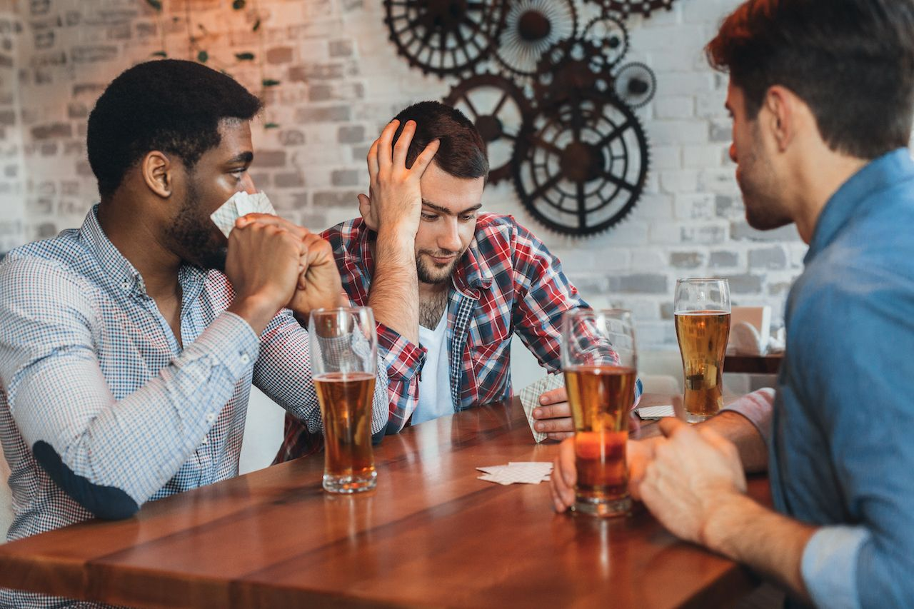 People at a bar with beer glasses drinking games without cards
