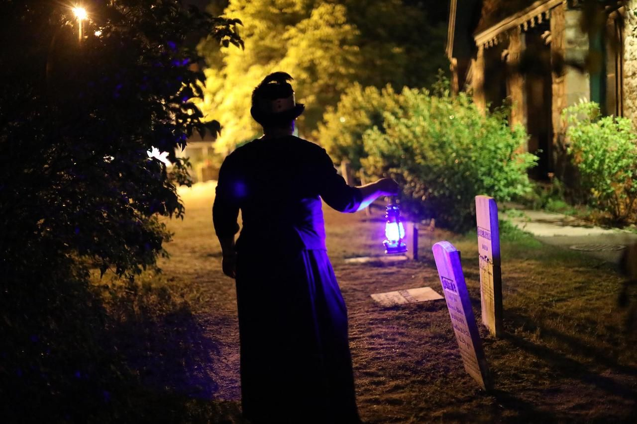 A Bar Harbor Ghost Tour guide holds up a blue lantern