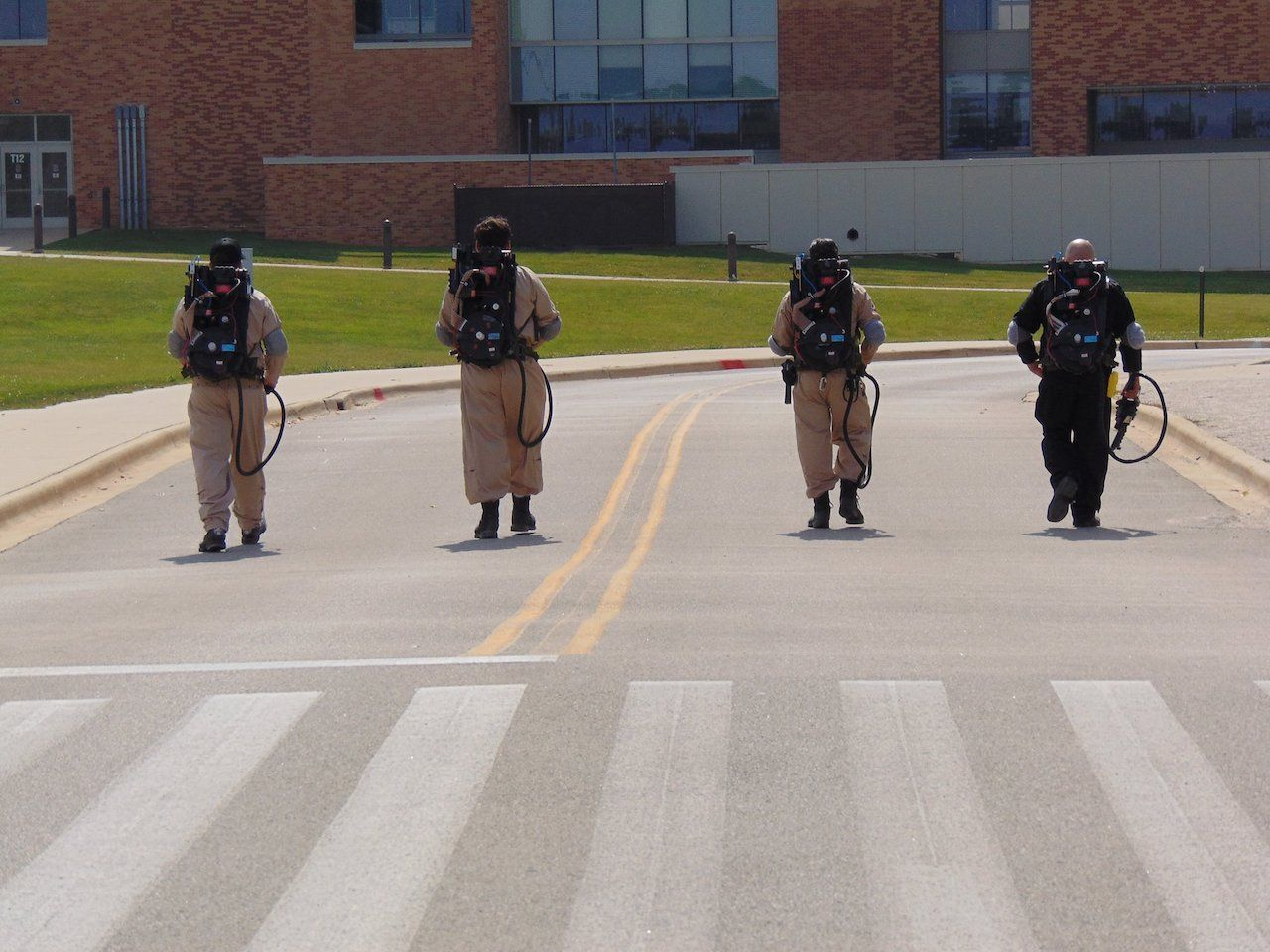 Four ghostbusters walk down an empty road on the Great Lake County Ghost Adventure in Illinois