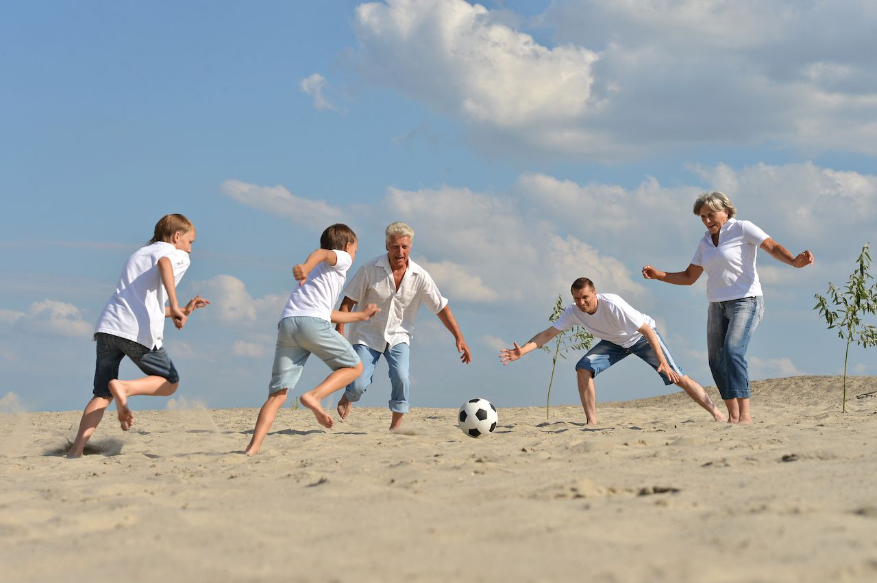 Family playing soccer on the beach on Thanksgiving