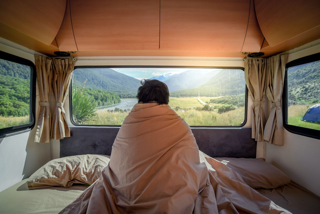 Guy in bed in a camper van