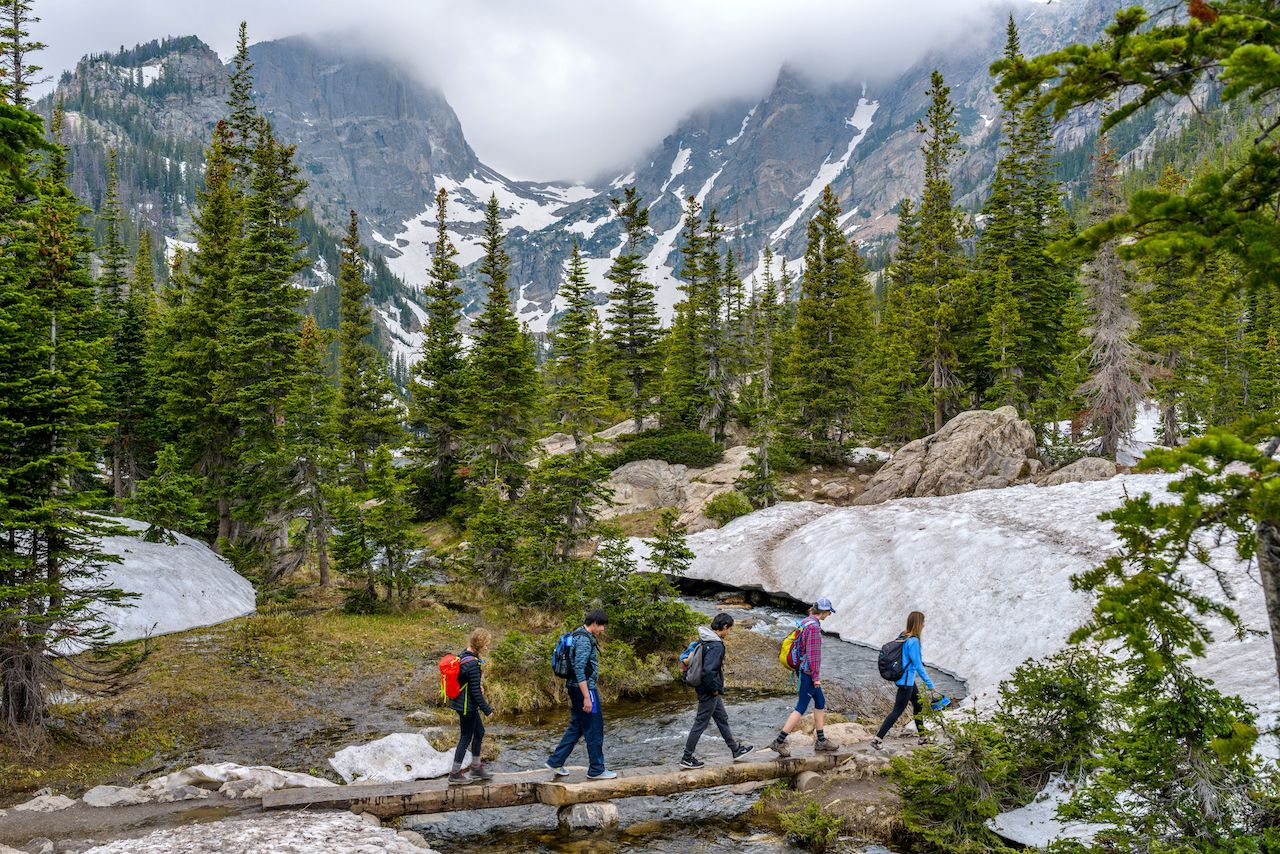 Hikers walking cross a tree trunk bridge over Tyndall Creek on Emerald Lake Trail
