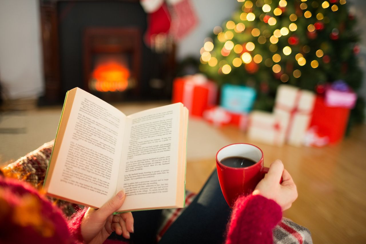 Reading a book by a Christmas tree