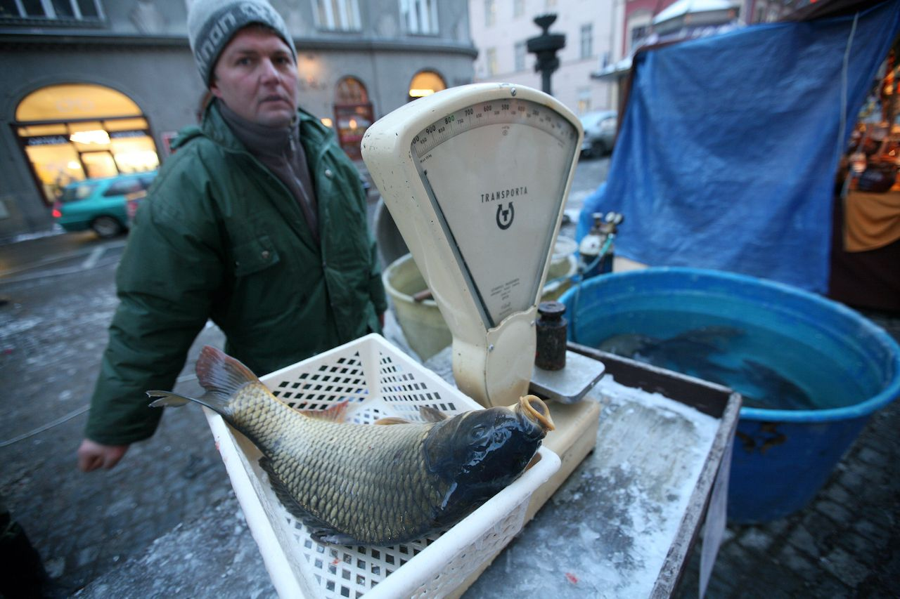 Vendor weighing a carp