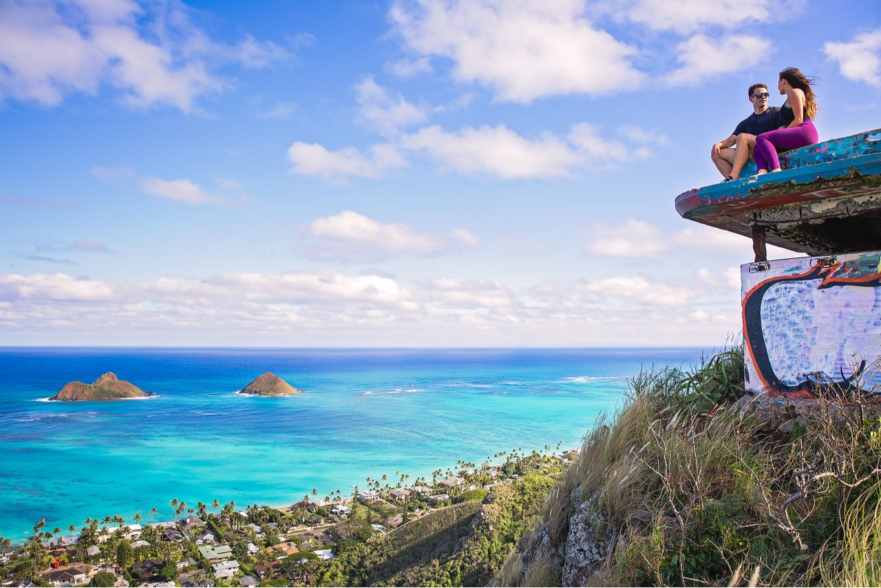 Young couple sitting on pillbox over looking Lanikai in Kailua Hawaii