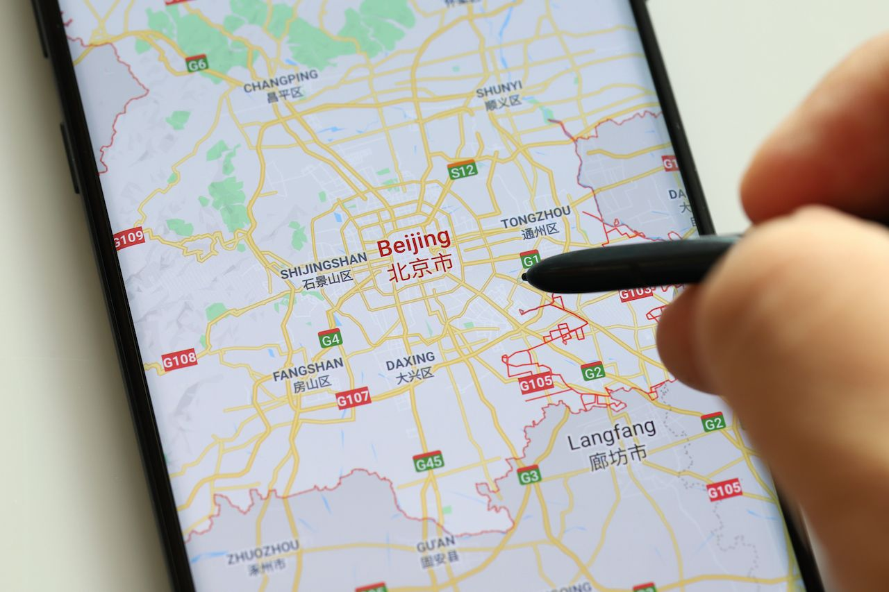 Hand holding stylus on phone using Google Maps in China, Google maps sustainability