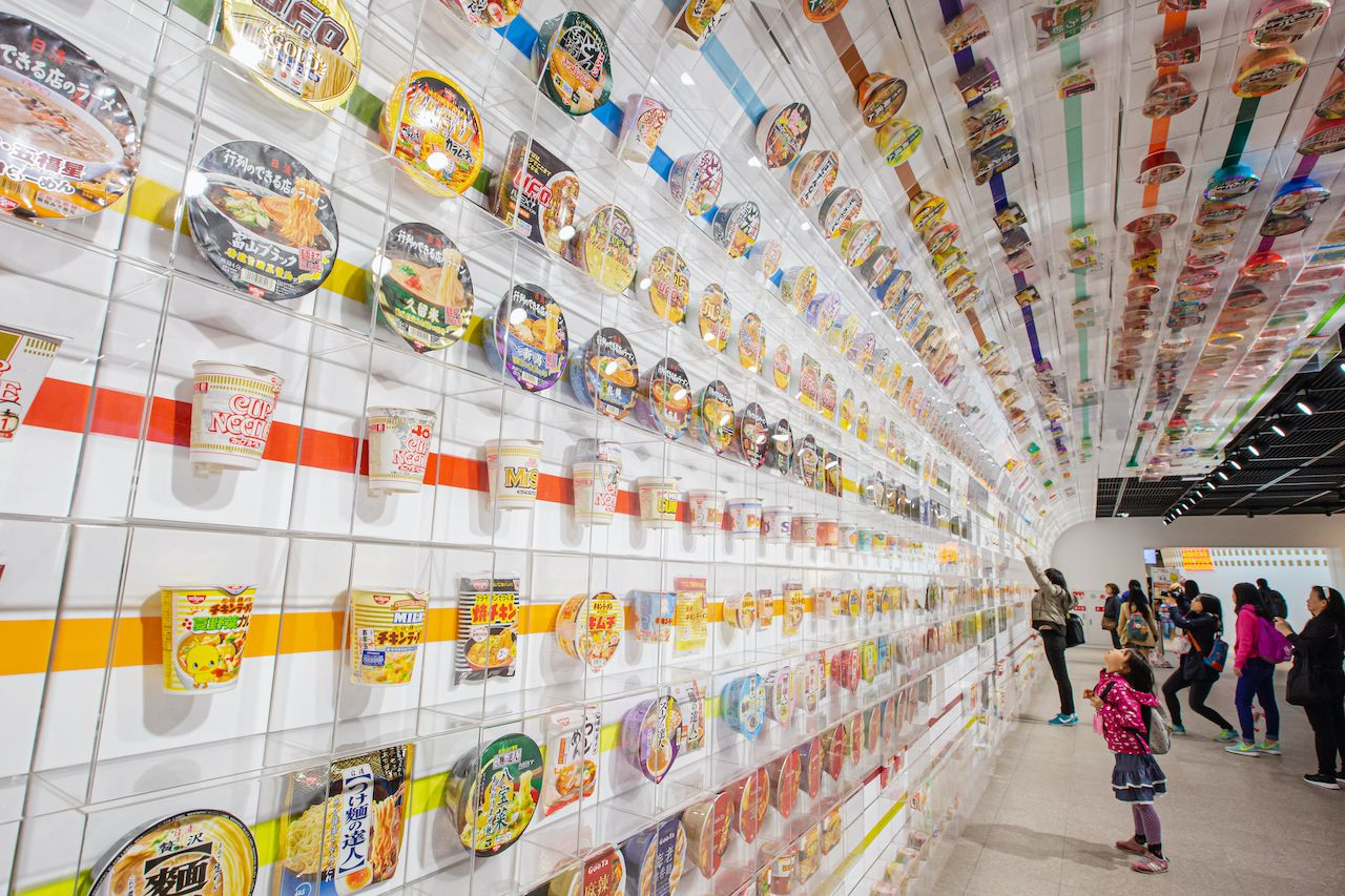 Little girl look up many cup noodles decoration on wall exhibition tell story about instant noodles at The Cup Noodles Museum Osaka., museums in Japan