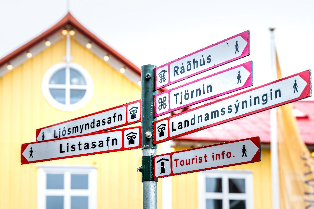 Reykjavik, road from Iceland to downtown and colorful yellow building sign outside the restaurant to go to points of interest, Icelandic culture