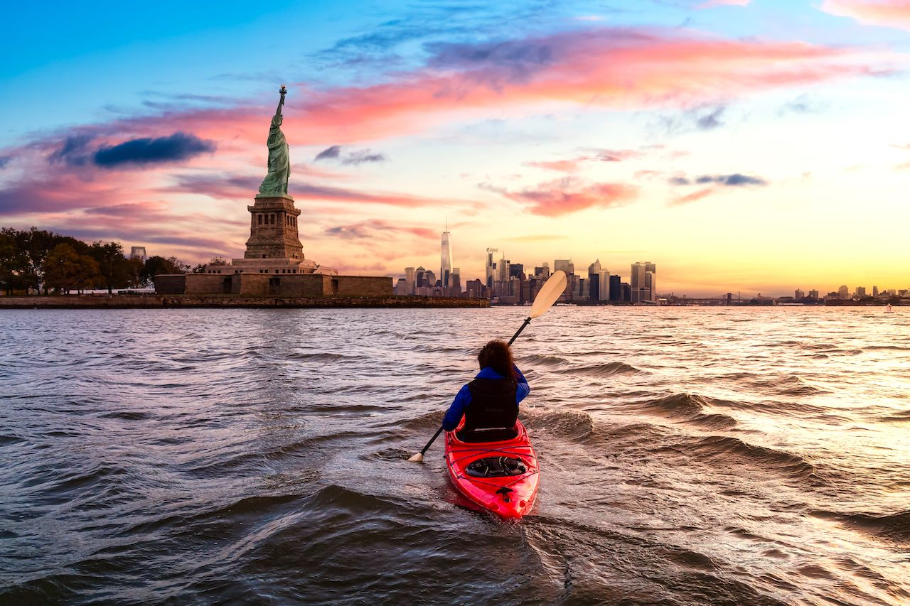 Woman Sea Kayaking near the Statue of Liberty. Colorful Sunrise, Outdoor events New York City 2021