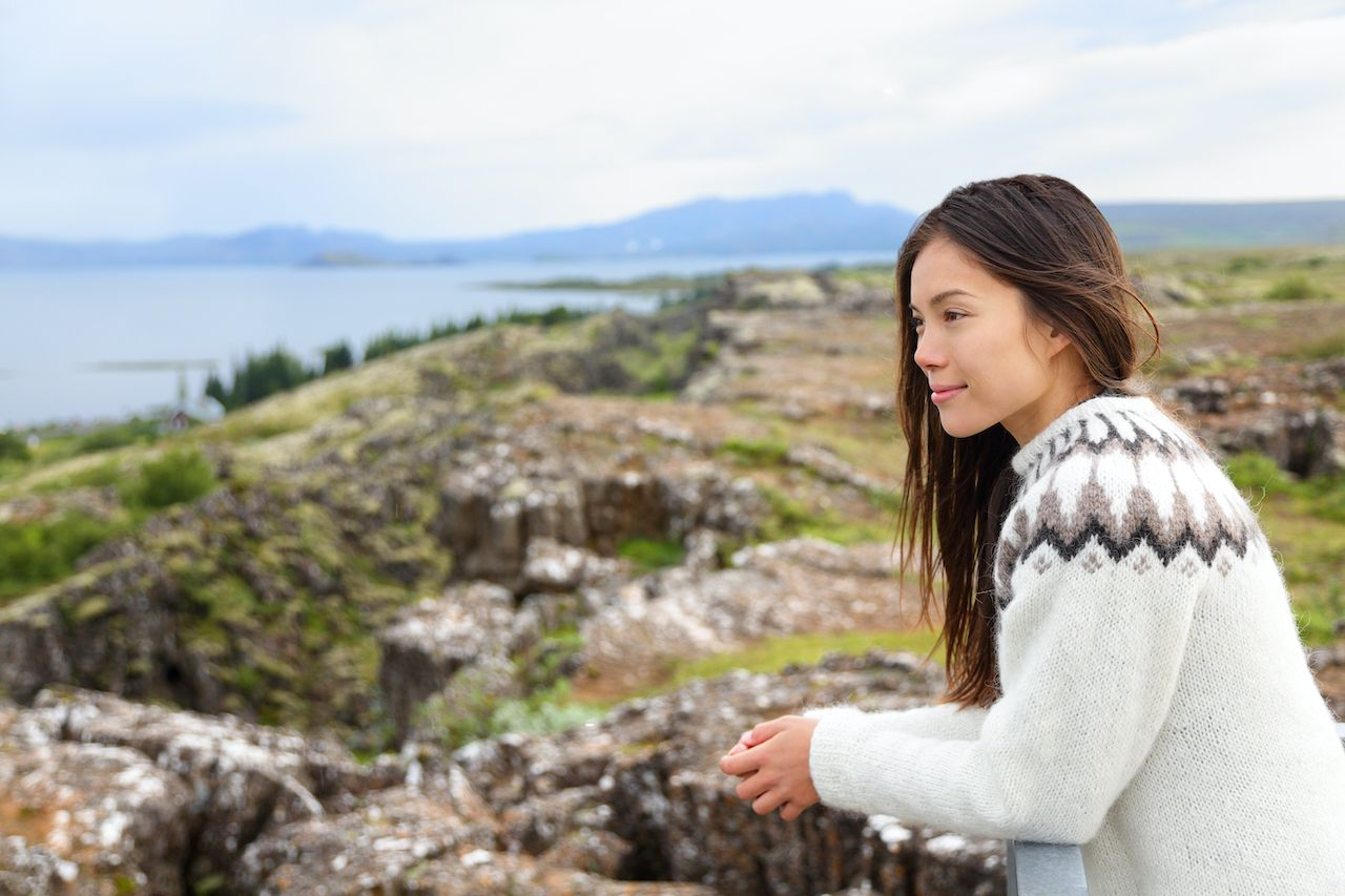 Iceland - woman in Icelandic sweater looking at Thingvellir place of Althing, the first parliament in the world. , Icelandic culture
