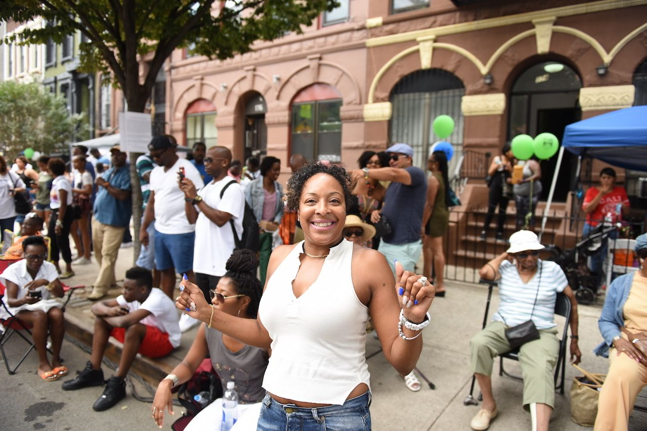 Woman celebrating block party, outdoor events in New York City 2021