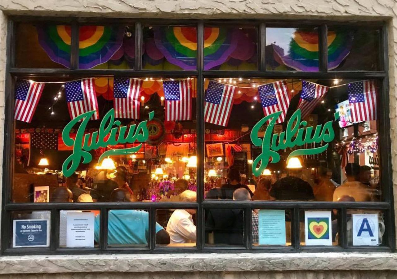 Outide of Julius bar decorated with american and gay flags, LGBTQ safe spaces US