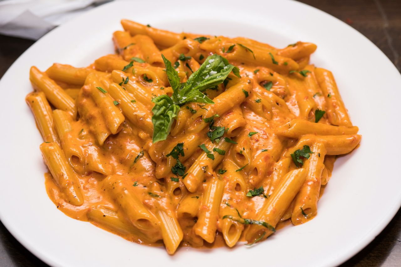 Table top shot of delicious beautiful prepared bowl of penne alla vodka noodles in pink tomato sauce at a gourmet restaurant, penne alla vodka