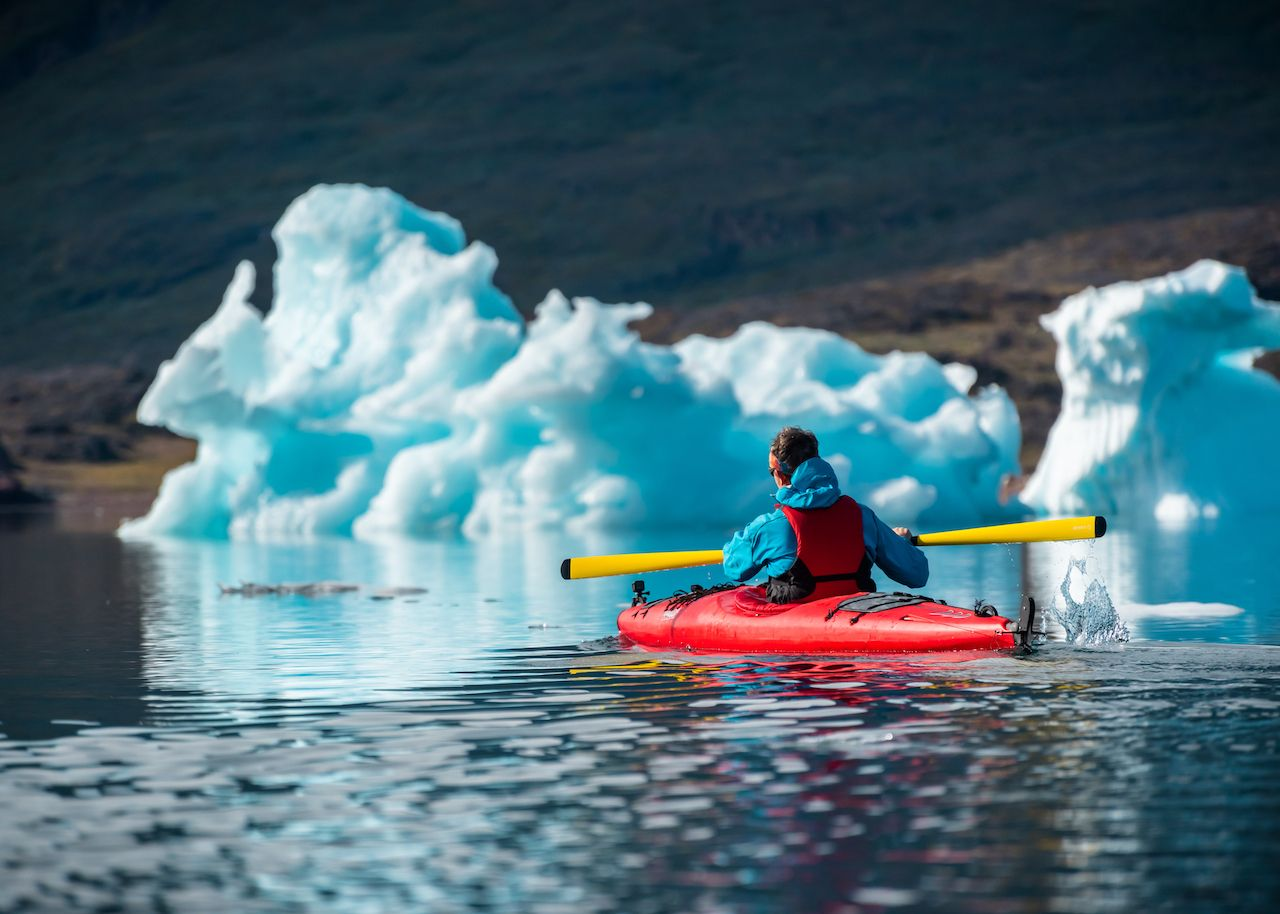 Greenland paddling alongside bergs