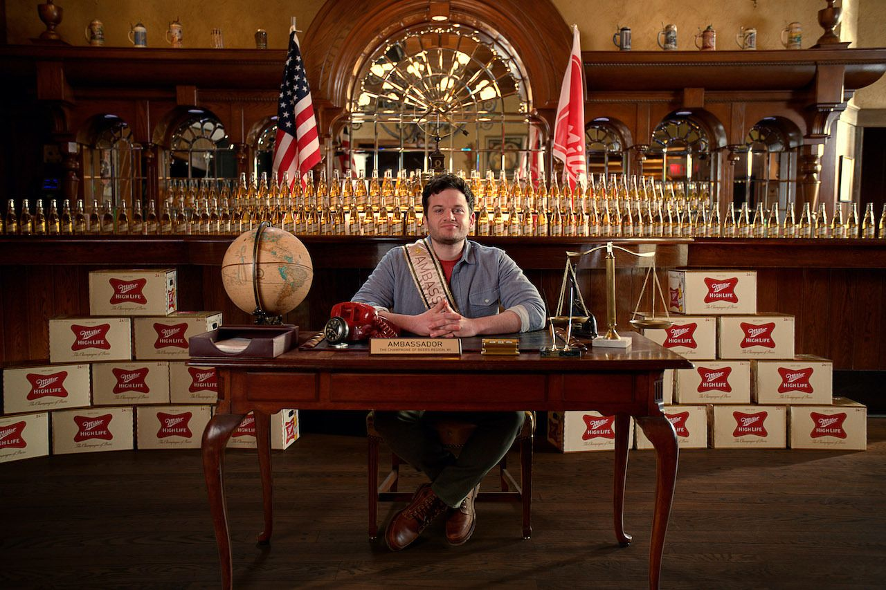 Miller High Life Champagne of Beers ambassador sitting in a desk, Miller high life