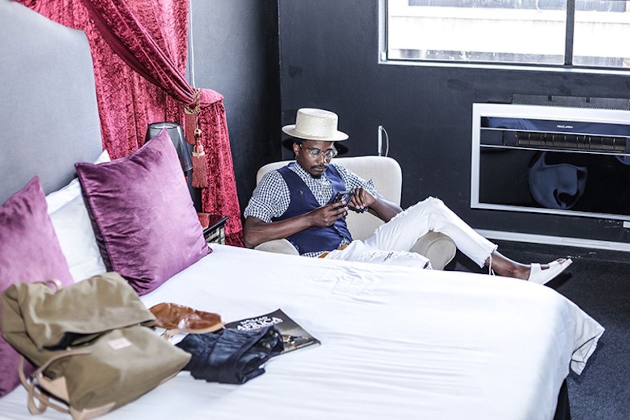 Person sitting in bedroom at The 12 Decades Art Hotel, Maboneng district Johannesburg