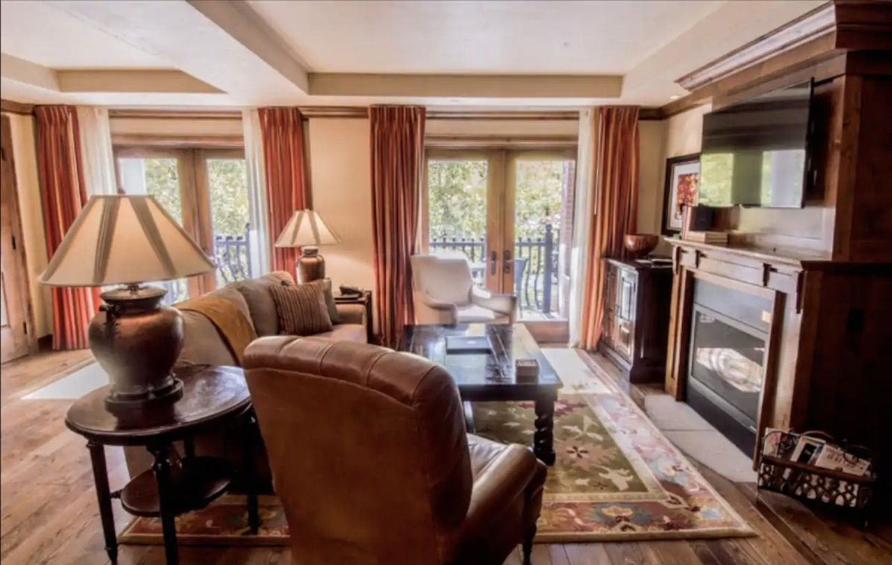 Two-bedroom condo in the Grand Hyatt living room with leather chair and couch, Airbnbs in Aspen