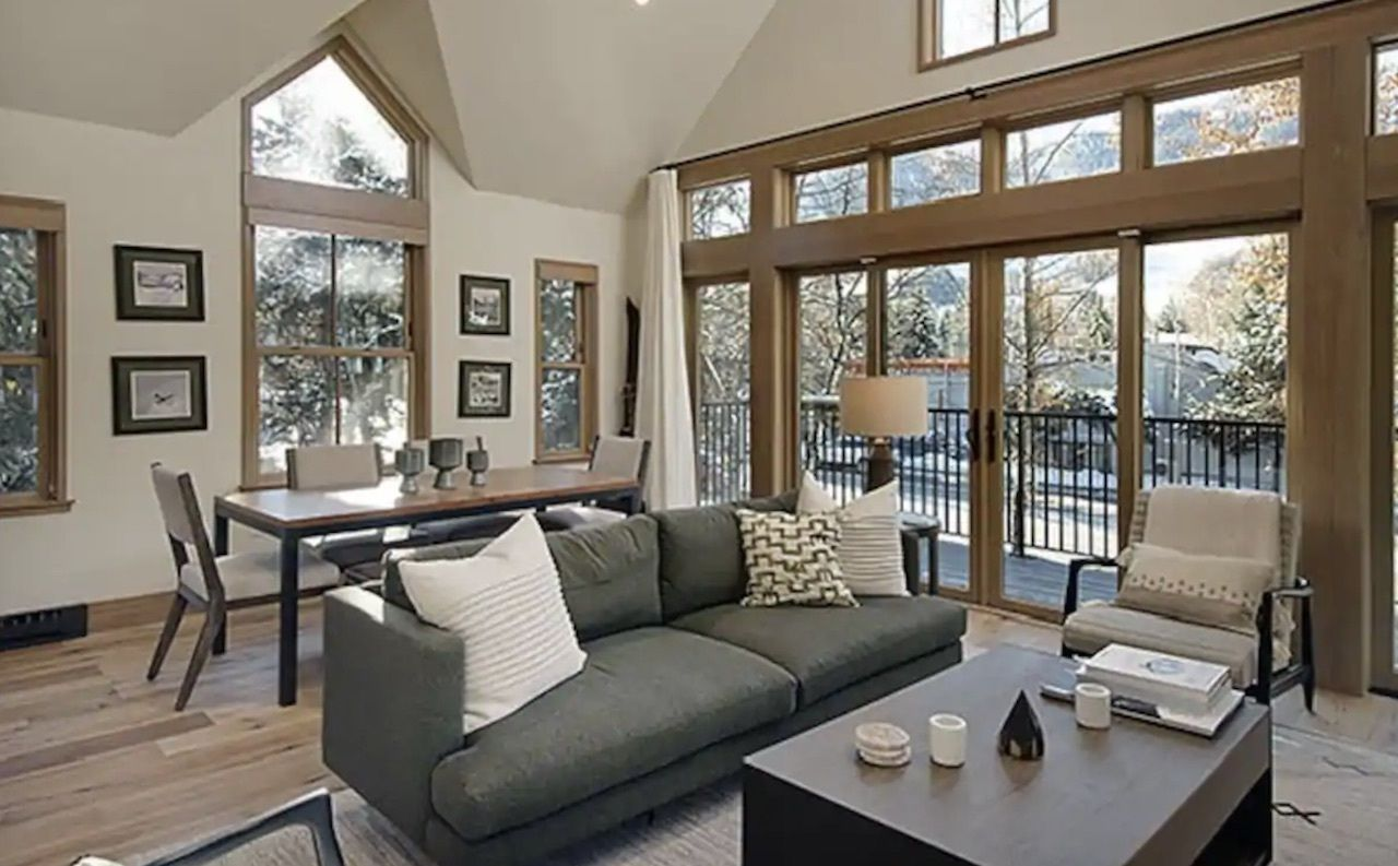 North Star Penthouse on Main Street, Aspen living room with large window and couch, Airbnbs in Aspen