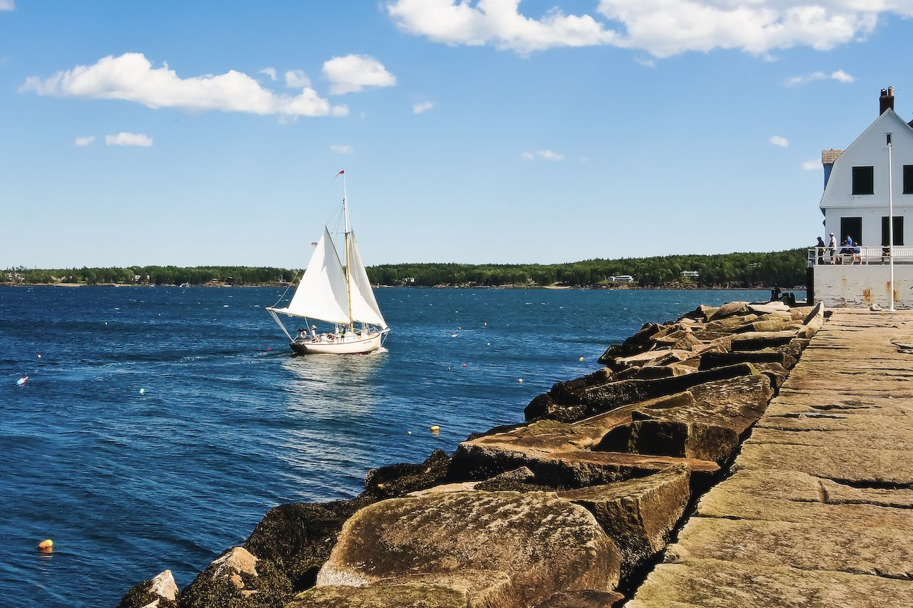 Beautiful view of Rock paved path to Rockland breakwater lighthouse and sailing boat in Rockland harbor Maine usa, August travel