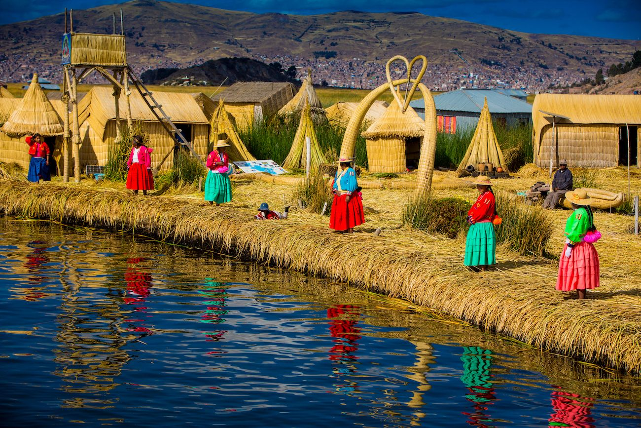 Local women waiting for visitors at the edge of the totora reeds island in the Uros Islands, Peru