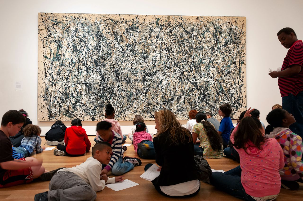 New York City, USA - June 9, 2010: Group of children in a class, sitting in front of a Jackson Pollock painting at the Museum of Modern Art in New York City, USA., the MoMA