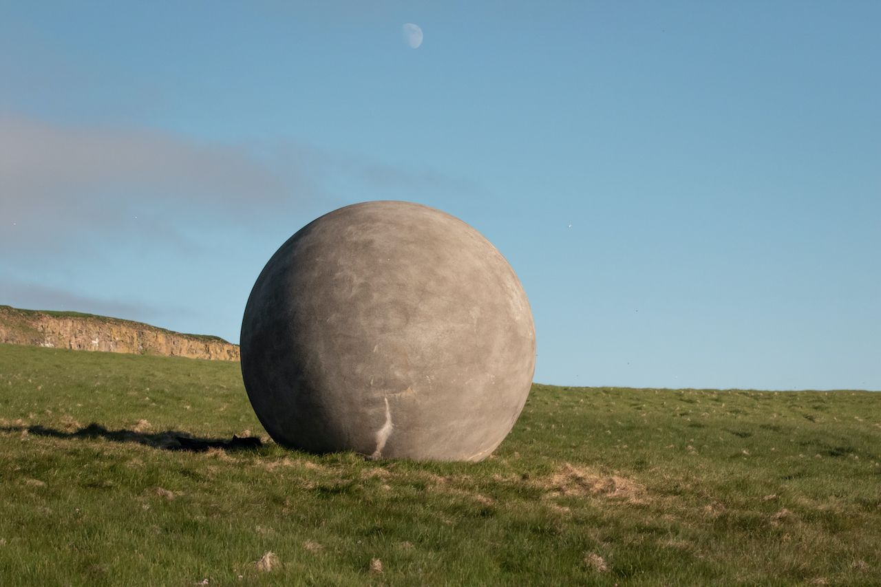 Grimsey / Iceland - August 02 2020: Orbis et Globus (Circle and Sphere) on the Arctic Circle in Grímsey Island, Iceland, green grass field and cliffs and blue sky on the background, Akureyri