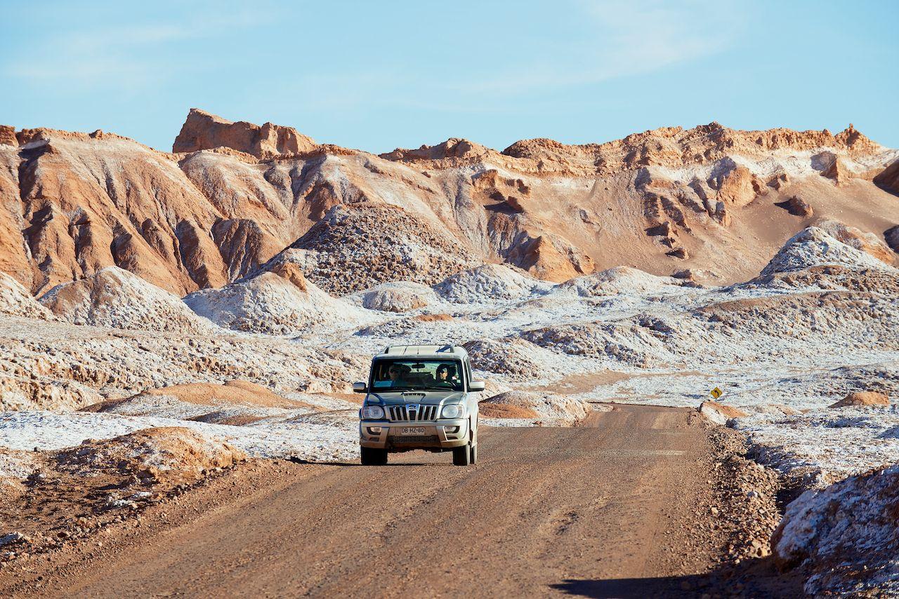 SAN PEDRO DE ATACAMA, CHILE - NOVEMBER 24, 2013: Unidentified people drive car in Valle de la Luna in San Pedro de Atacama, Chile., Atacama Desert